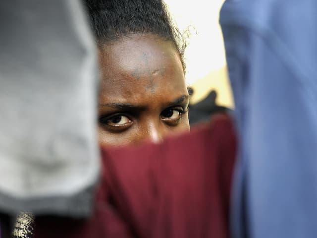 Eine schwarze Frau versteckt ihr halbes Gesicht hinter enem roten Tuch.