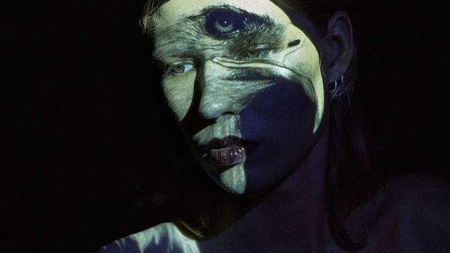 Eine Frau vor schwarzem Hintergund wird von einem surrealen Bild beleuchtet, sodass ein Auge auf ihrer Stirn zu sehen ist.