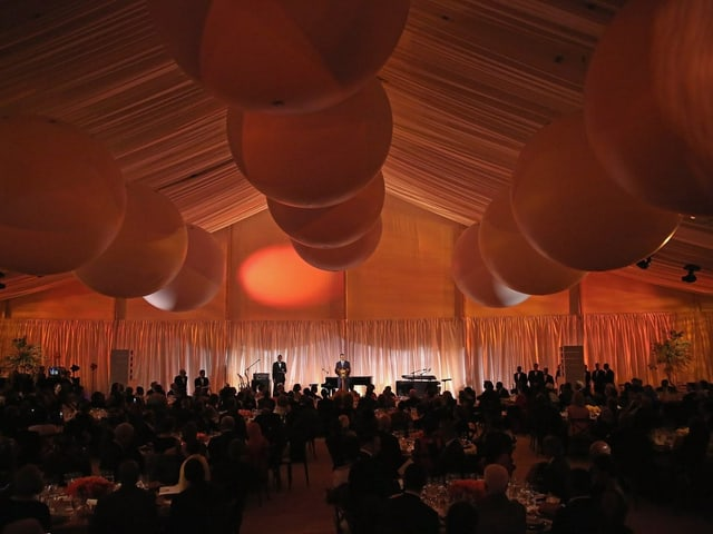 Innenansicht: Gäste sitzen an den Tischen, Obama hält auf der Bühne seine Rede, das Ganze in oranges Licht getaucht.