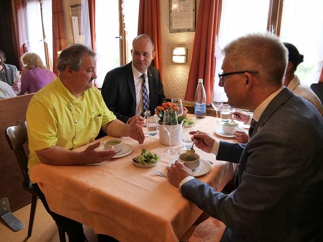 Ein Vierertisch. Die Runde isst Suppe und diskutiert.