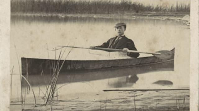 Foto des Jungen im Anzug auf einem Kajak im See.