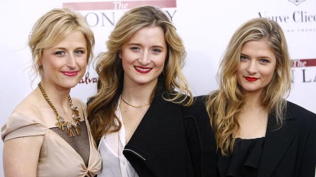 Drei blonde Frauen blicken in die Kamera