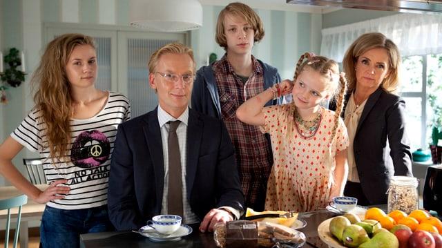 Ein Mann und eine Frau mit ihren zwei Töchtern und ihrem Sohn posieren in der Küche für ein Familienfoto.