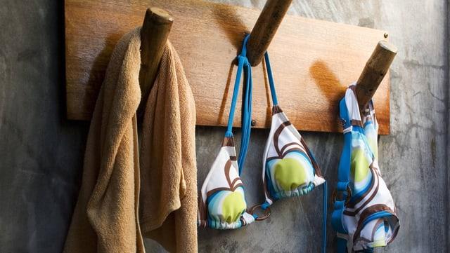 Bikini und ein Handtuch hängen in einem Umkleiderum an einer hölzernen Garderobe.