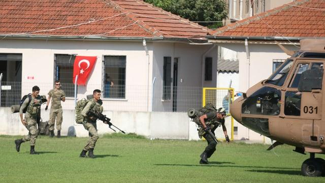 Soldaten laufen in geduckter Stellung zu einem Armeehelikopter