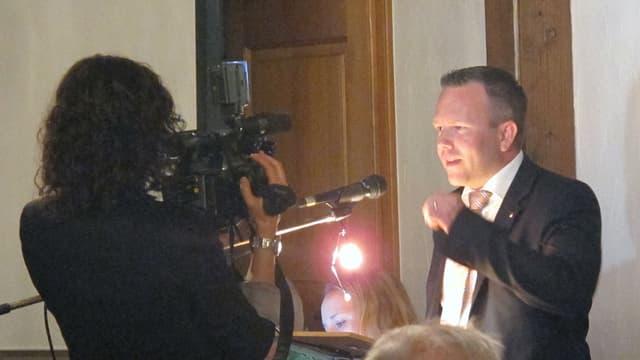 Eine Kamerafrau steht direkt vor Silvio Jeker während seiner Rede.