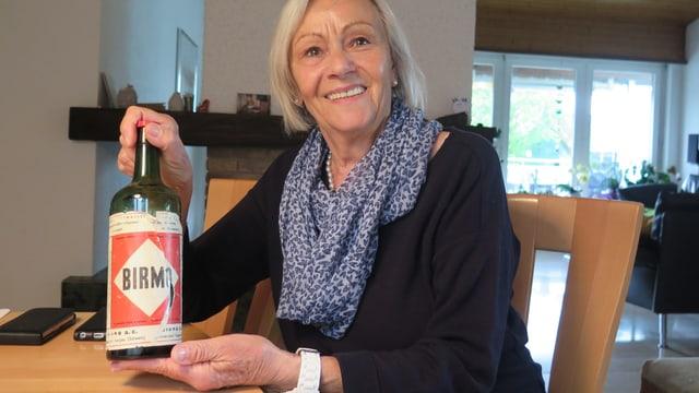 Eine Frau hält eine Flasche