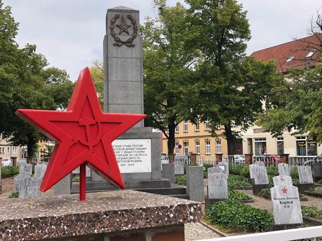 Gräber mit rotem Stern. Davor ein roter Stern mit Hammer und Sichel als Zeichen der Sowjetunion.