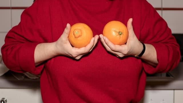 Eine Frau hält zwei Orangen in den Händen.