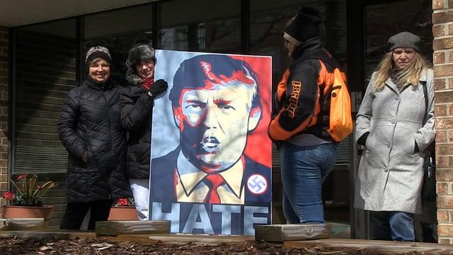 Frauen, die ein gemaltes Donald Trump Porträt halten, darauf steht «Hate» und ein Hackenkreuz ist sichtbar.