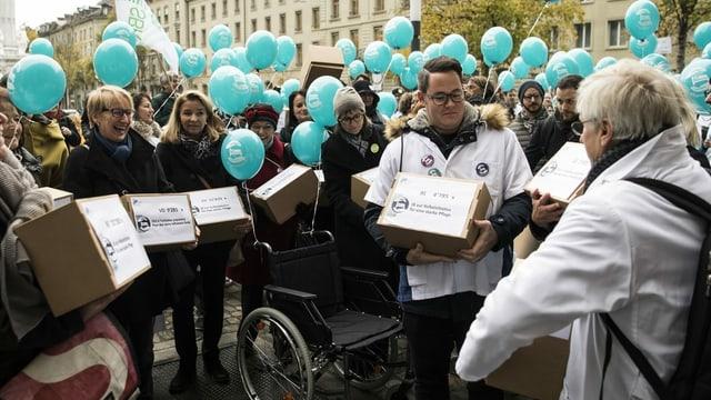 Verschiedene Pflegefachpersonen in weissen Kitteln reichen die Unterschriften zur Pflege-Initiative vor dem Bundeshaus ein.