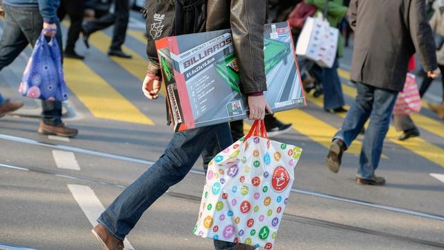 Symbolbild: Nicht identifizierbare Menschen mit Einkaufstaschen überqueren eine Strasse.