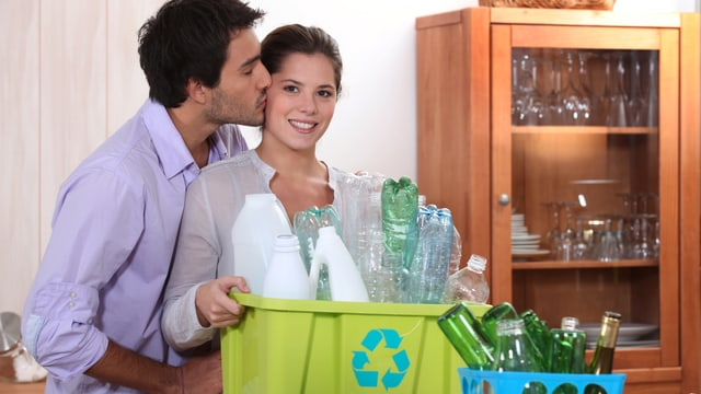 Mann gibt Frau einen Kuss, die eine Recyclingkiste in der Hand hat.