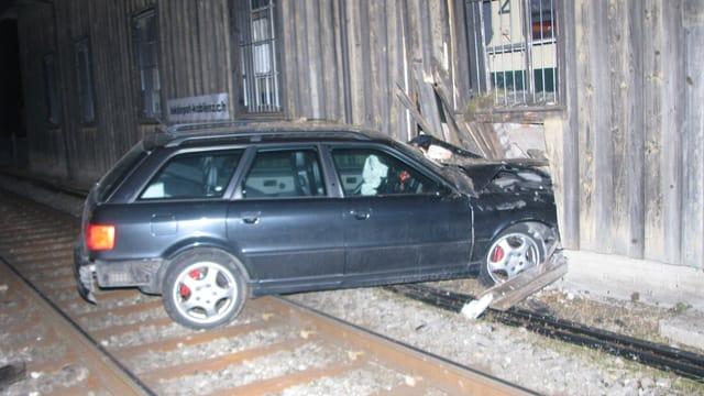 Unfallauto steht halb im Gebäude, halb auf den Geleisen