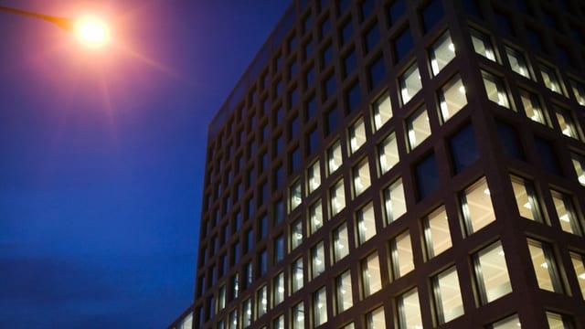 Ein neues Bürogebäude in Nahaufnahme bei Nacht.