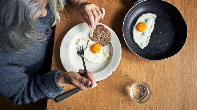 Eine ältere Frau sitzt am Tisch und isst Spiegeleier mit Brot.