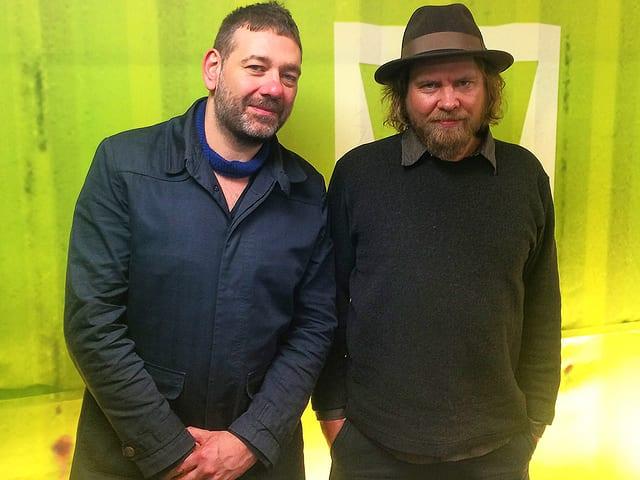 Darius und Danny von Archive stehen vor dem grünen Virus-Logo