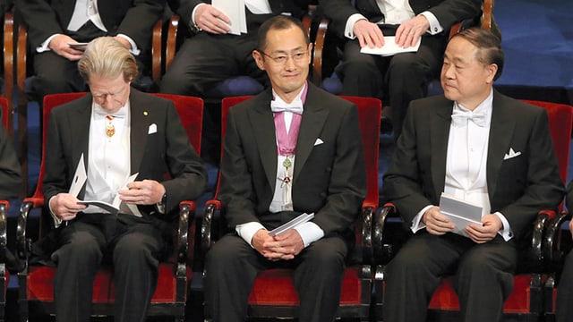 Ein Japaner im Anzug und mit Brille, lächelnd.