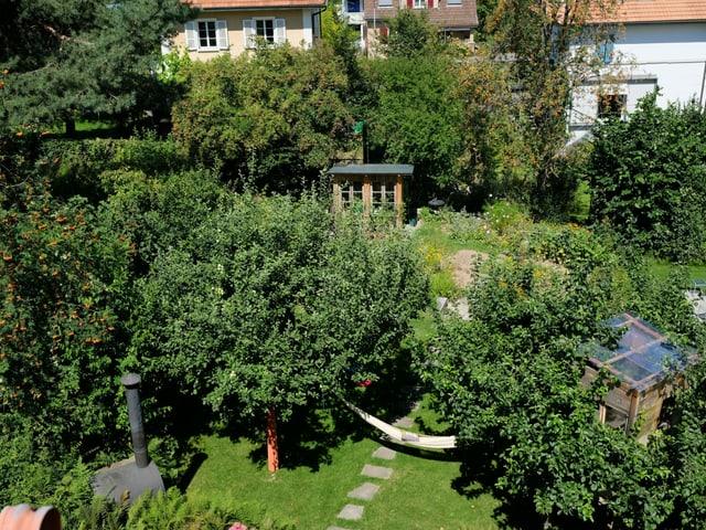 Ein Garten mit Bäumen, Hecken, Blumen und einem Gartenhäuschen