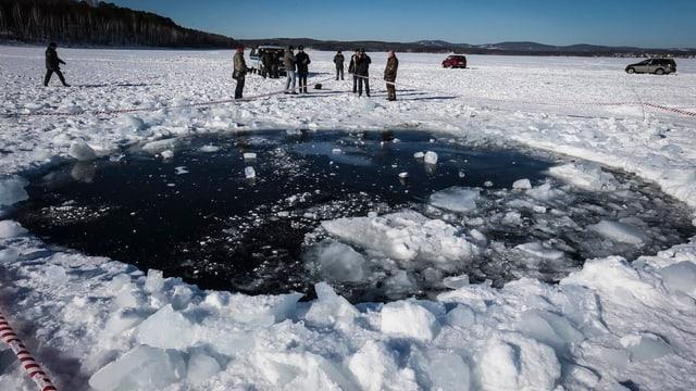 Gefrorener See mit einem Loch.