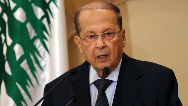 Mann an Rednerpult, libanesische Flagge im Hintergrund.