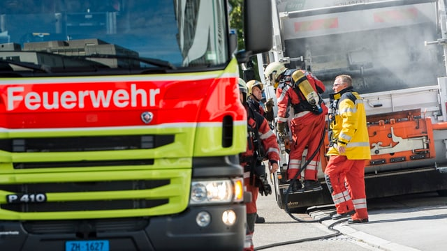 Ein Feuerwehrauto, dahinter Feuerwehrmänner