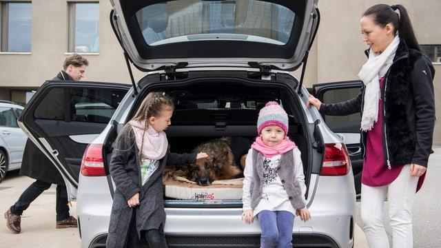 Ein Hund im Heck eines Autos und Kinder sind nebenan.