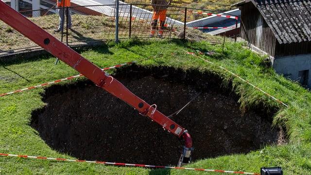 Ein grosses Loch in einer Wiese.