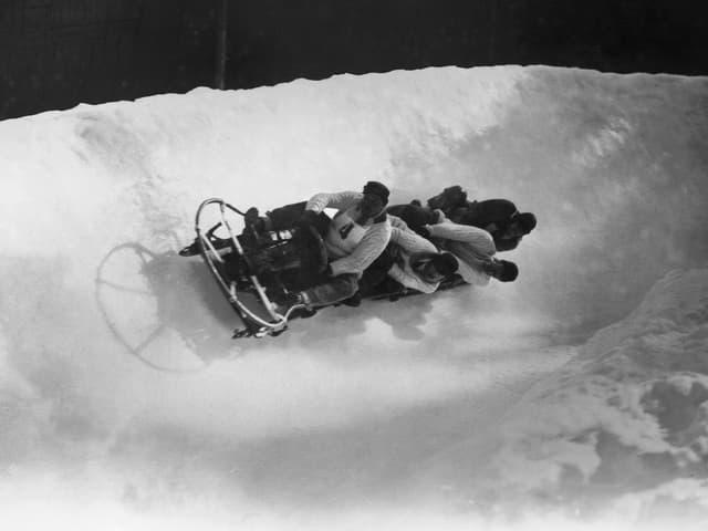 Ein Bob, bestehend aus einem Gestell mit Kufen, darauf sitzen 4 Männer, gerade in einer Kurve liegend.