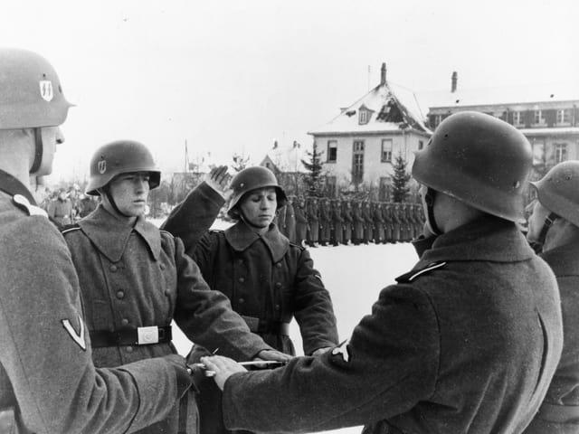 Schwarzweissfoto: Ein Mann in Uniform hebt die Hand zum Schwur. Er ist umgeben von weiteren Soldaten, im Hintergrund steht eine ganze Einheit Spalier.