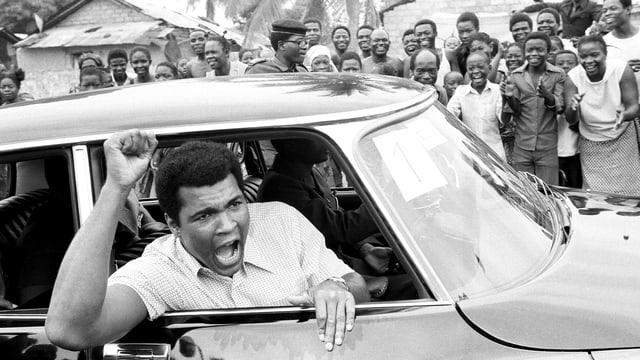 Der Boxer Muhammad Ali schreit aus einem Auto zu seinen Fans im Kongo.