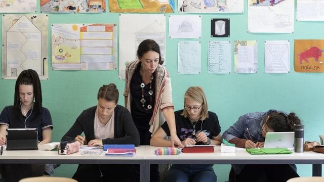 Scolaras e scolasta concentrada en scola.