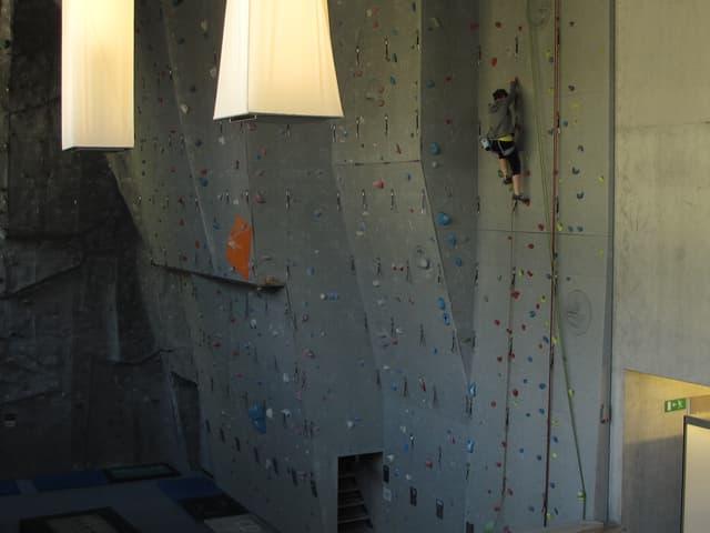 Frau klettert an Kletterwand