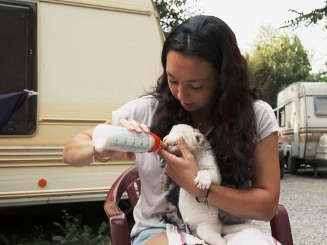 Frau füttert einen Babylöwen mit einer Milchflasche.