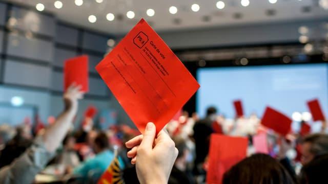Eine Frau hält an der Versammlung der SP eine rote Wahlkarte in die Höhe.