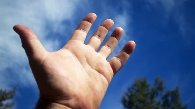 Hand vor blauem Himmel.