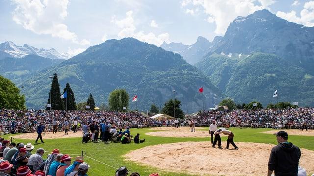 Im Vordergrund die Schwingplätze aus Sägemehl auf einer Wiese. Rundherum Zuschauer auf Tribühne. Im Hintergrund Bergpanorama.