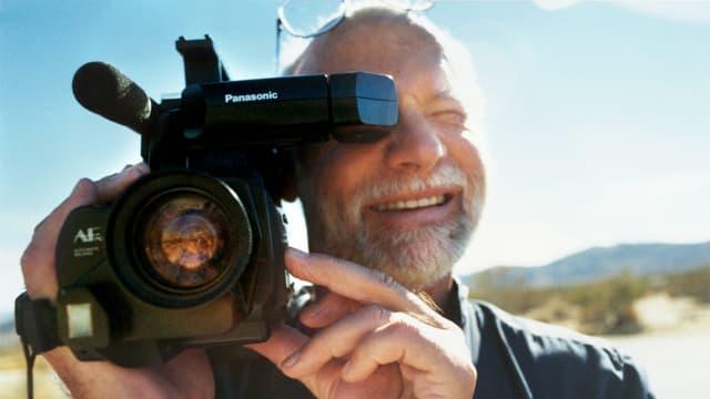 Ein Mann mit Bart filmt lächelnd mit einer VHS-Kamera.