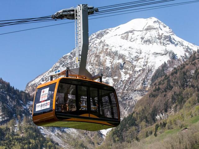 Neue orange Gondelbahn mit Berg im Hintergrund