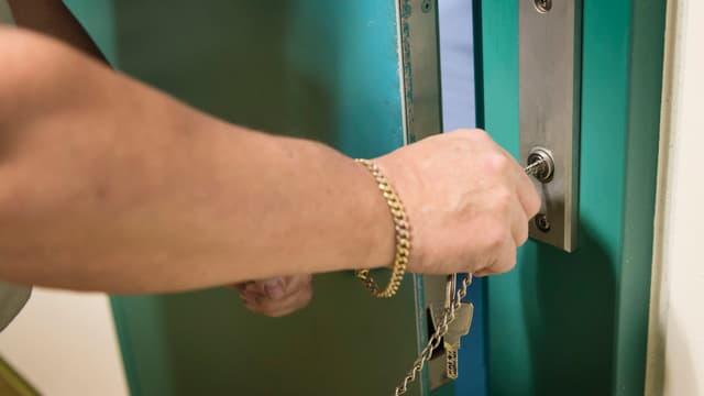 Ein Aufseher schliesst eine Gefängniszelle ab