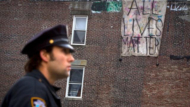 Polizist vor einem Backsteinhaus an dem ein Transparent hängt.
