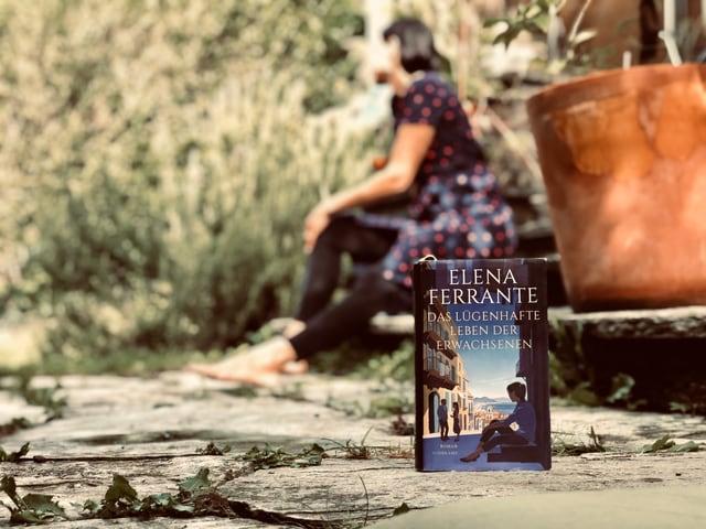Der Roman «Das lügenhafte Leben der Erwachsenen» von Elena Ferrante steht im Vordergrund. Im Hintergrund sitzt Annette König auf einer Steintreppe.