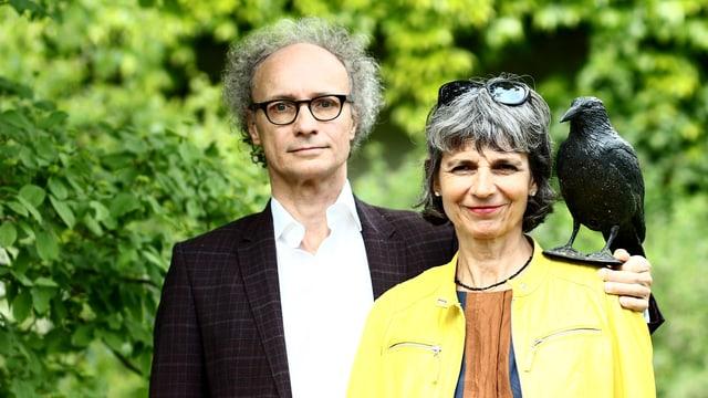 Porträtaufnahme des Paares. Sie stehen vor grünen Büschen. Er trägt schwarzen Kittel und weisses Hemd, sie eine gelbe Jacke. Auf ihrer linken Schulter hält er eine Rabenfigur.