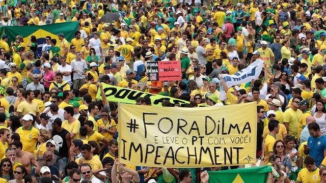 Dicht gedrängt stehen Demonstranten mit gelben T-Shirts auf der Strasse und fordern auf Transparenten ein Amtsenthebungsverfahren gegen «Dilma».