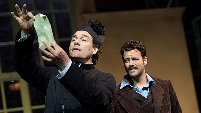 Ein Mann in Pfarrerskleidung hält einen Geldschein hoch, dahinter ein Mann in Anzug mit Gilet.