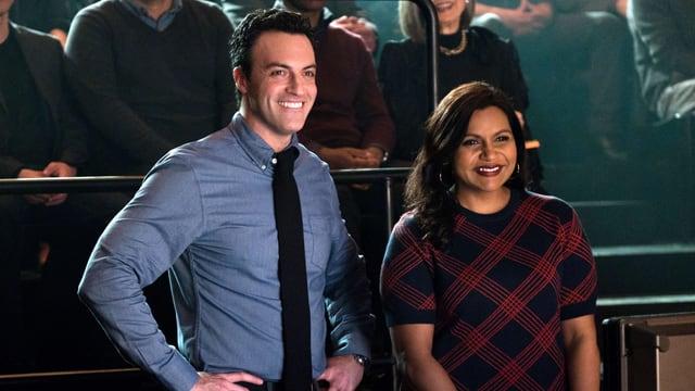 Ein Mann mit Hemd und eine Frau in Kleid stehen lachend nebeneinander und schauen in die gleiche Richtung.