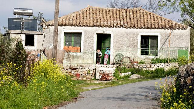 Kinder stehen im Eingang eines Einfamilienhauses.