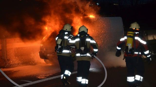 Drei Feuerwehrleute löschen in der Dunkelheit ein brennendes Auto.