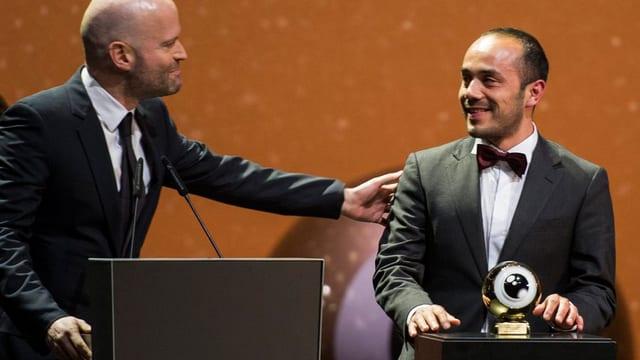 Ein Mann in dunklem Anzug steht vor einem Pult und blickt zu einem Mann im Anzug, der eine Trophäe vor sich stehen hat.