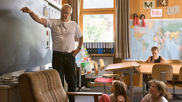 Ein Lehrer steht an der Wandtafel.